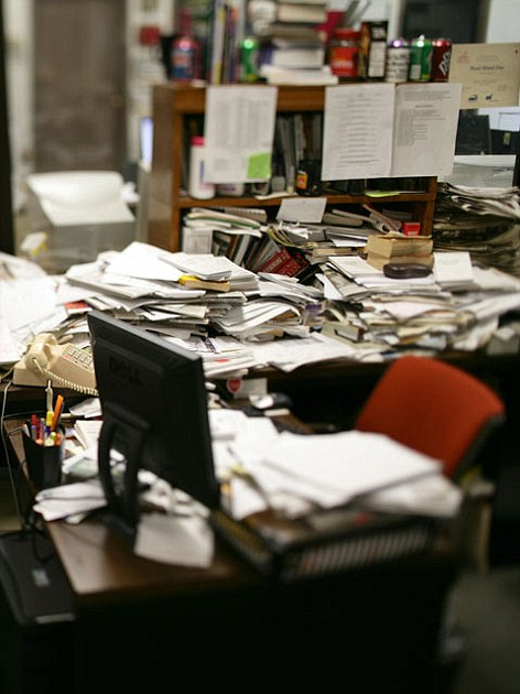 A messy desk with lots of paperwork